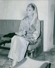 Woman siting and looking away, holding diary.