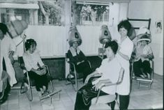 Woman grooming another woman and smiling in  salon . 1968