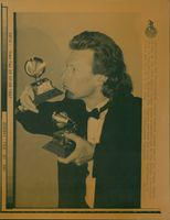 Steve Winwood kisses one of two Grammy Awards he won at the 29th Annual Grammy Award.