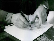 Man painting with pen on paper.