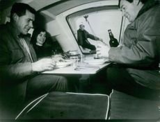 Men and woman inside a boat at Boat Show in Paris 1969