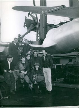 A group of men posing for the camera beside an aircraft. 1954.