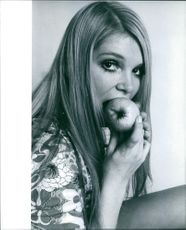 Photograph of Eva Rueber-Staier while she was eating Apple.  Eva Rueber-Staier (sometimes spelled Eva Reuber-Staier) is an Austrian actress, TV Host, model and beauty queen who won Miss World 1969.