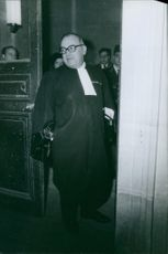 A judge standing at the door of the court room.
