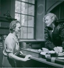 A woman talking to a librarian, 1940.