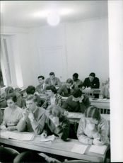 Students in the classroom writing something.