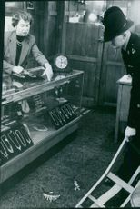 A photo of a two man in a jewelry shop and the jewelry are falling in the floor.
