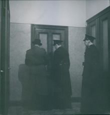 Policemen standing and tying to open the door.