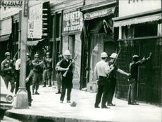 Group of soldiers and policemen, one officer is searching a man whose hands is on the wall.  Taken - 23 July 1967