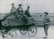 Sgt. William Coyne, of Royal Scottish Fusiliers, of Beath, Ayrshire, talks to Russian girl medical orderly riding on a cart in Soviet Convoy, together with two soldiers. Germany, July 5, !945