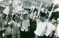 People celebrating, waving their banners, smiling, in the side street of Saigon, a city in Vietnam, November 1972.