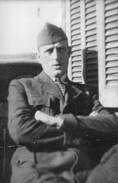 Vintage photo of a soldier in his uniform and arms crossed.