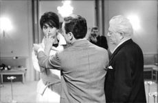 Sophia Loren standing with men, finger on her nose.