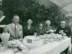 A family gathering with a priest, foods on table.  Taken - Circa 1965