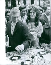 Dalida and Lucien Morisse with confetti in their hair, standing beside a table with records on it.