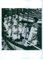 Group of old women wearing sailor uniforms on a boat.