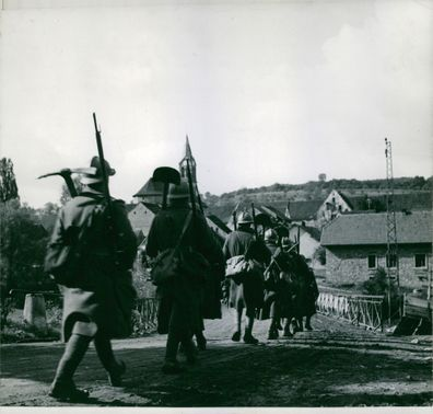 French soldiers in a long line as they march towards a village.