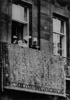 Queen Juliane holding a child outside on a balcony.