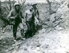 Soldiers carrying a prisoner.