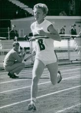 Patricia Lowe running on race track.