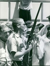 Cop standing with rifle among people.