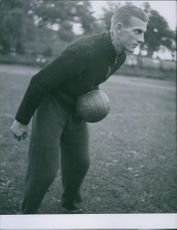 Footballer holding football and practicing in the ground. 1942