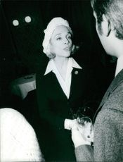 Micheline Presle talking to a man in a party.