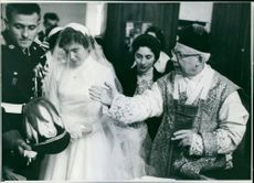 Bride and groom following ritual activity, priest standing beside instructing them.