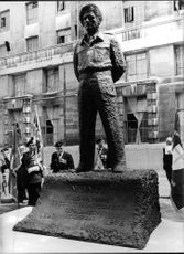 """People lookig at """"The Monty Statue""""."""