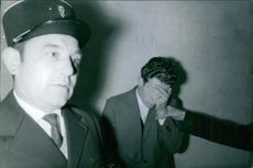 Roger Bossuet hiding his face beside the cops in France.