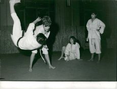 A woman practicing Judo techniques, sweeping hip her opponent, with two judoka, women, watching, December 1961.