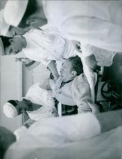A man in a stretcher surrounded by nurses and doctors in a healthcare center.