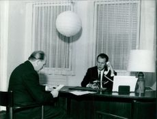 Prince of Naples Vittorio Emanuele having conversation in telephone in his office, while a man sitting opposite of the table, 1967.