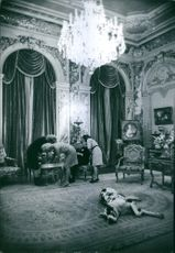 Man and women siting in the royal house, while cattle lying on the floor.