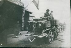 Men siting and transporting goods by cart in the street.