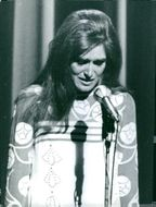 Dalida standing in front of microphone, with sad face, 1967.