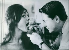 """Jean Desailly played as Dr. Francis and Daliah Lavi as Marie in a scene from the  1961 French film, """"Kväll på stranden"""" (English:  One evening on the Beach)."""