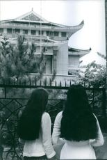 Two women looking at house.