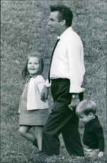 Children walking with their father in field. 1972