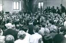 Alain Bombard being surrounded by a huge crowd of people and the media in an event, 1965.
