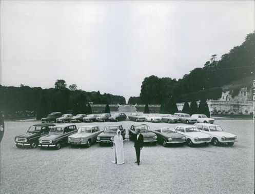 A MAN & WOMEN STANDING IN FRONT OF CARS