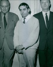 A man on handcuffs standing in between men. 1964