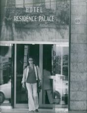 A woman walks out of the hotel doorway.