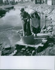 An Englishman in Sweden helping a woman wash the clothes beside the river during the German occupation in Norway, 1940.