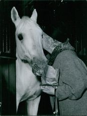 Man standing and kissing horse in the stable, holding packet.