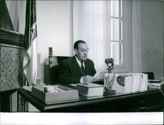 Ferhat Abbas sitting on his desk, 1961.