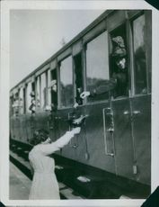 Woman standing at the platform, man communicating with her from train and smiling.