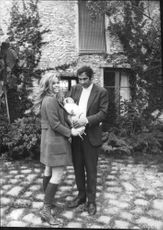 Roger Vadim standing with his wife.