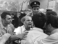 Old man with blood dripping from his face is talking to men in Israel.