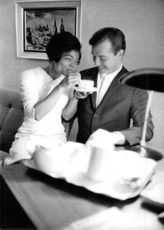 Eartha Mae Kitt having tea with a man.
